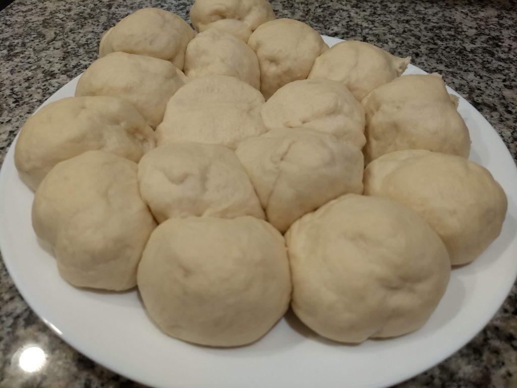 homemade naan dough balls resting on a plate
