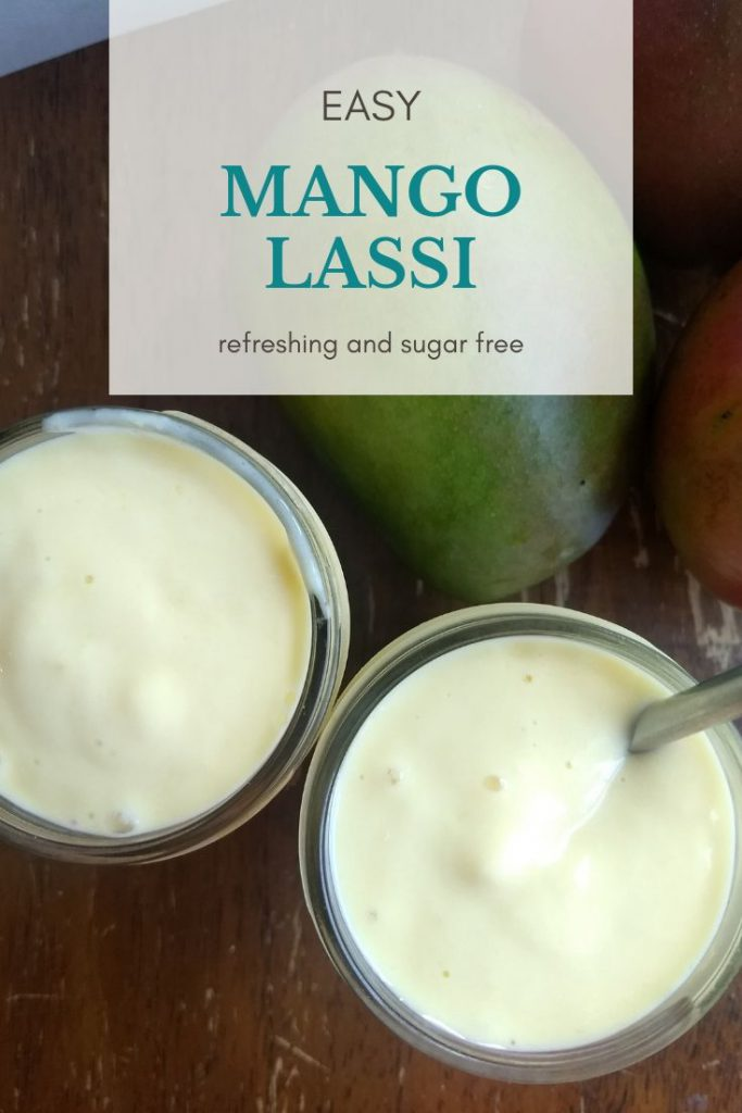 2 glasses of mango lassi and fresh mangos on a wooden table