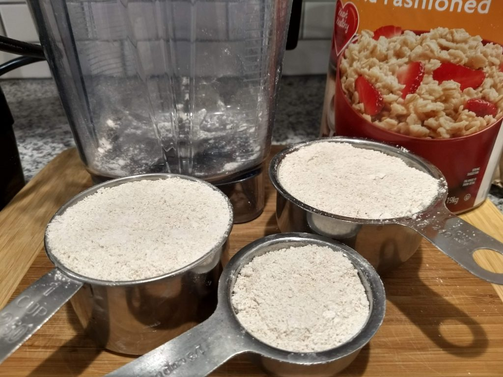 measuring cups with homemade oat flour. If you've ever wondered how to make oat flour, this post will tell you how.