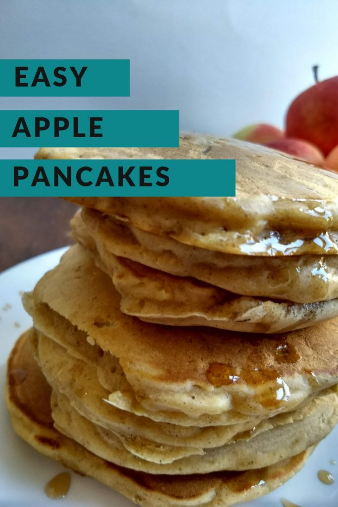 close up shot of whole wheat apple pancakes stacked on a plate with a bowl of apples next to them