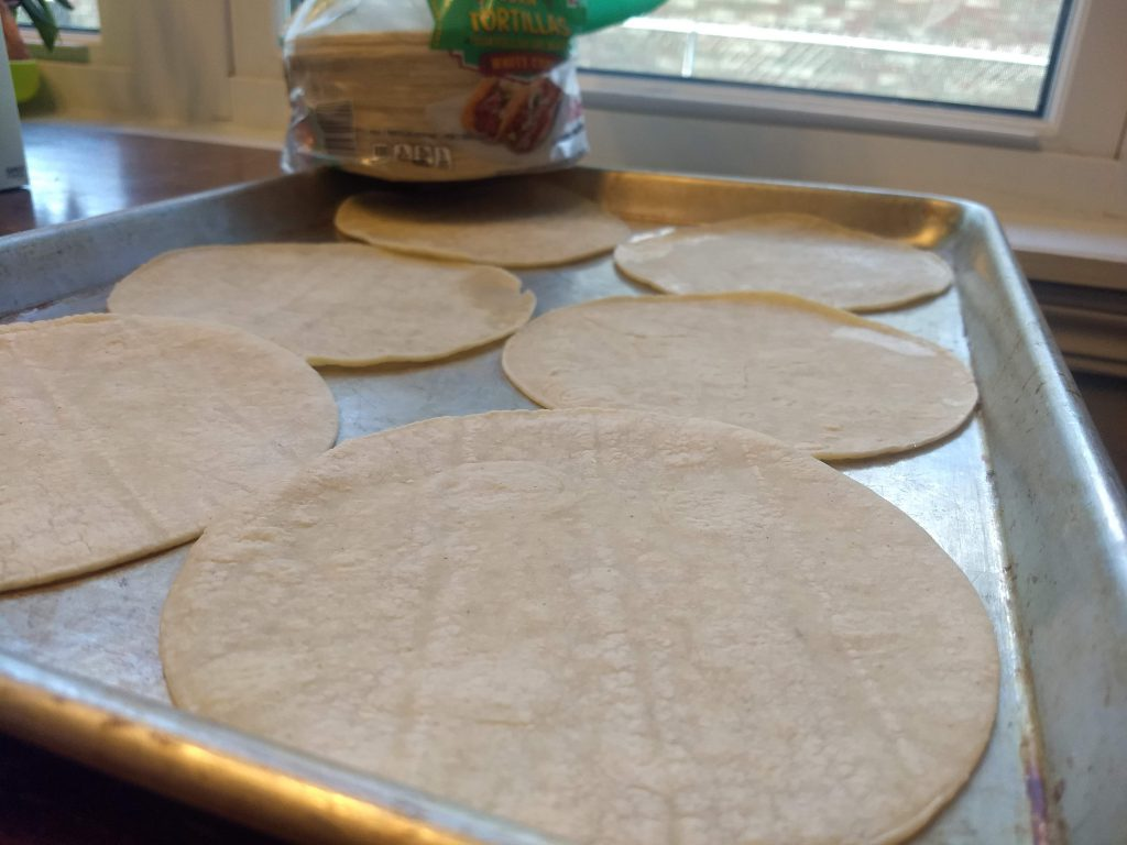 upbaked corn tortillas on a baking sheet