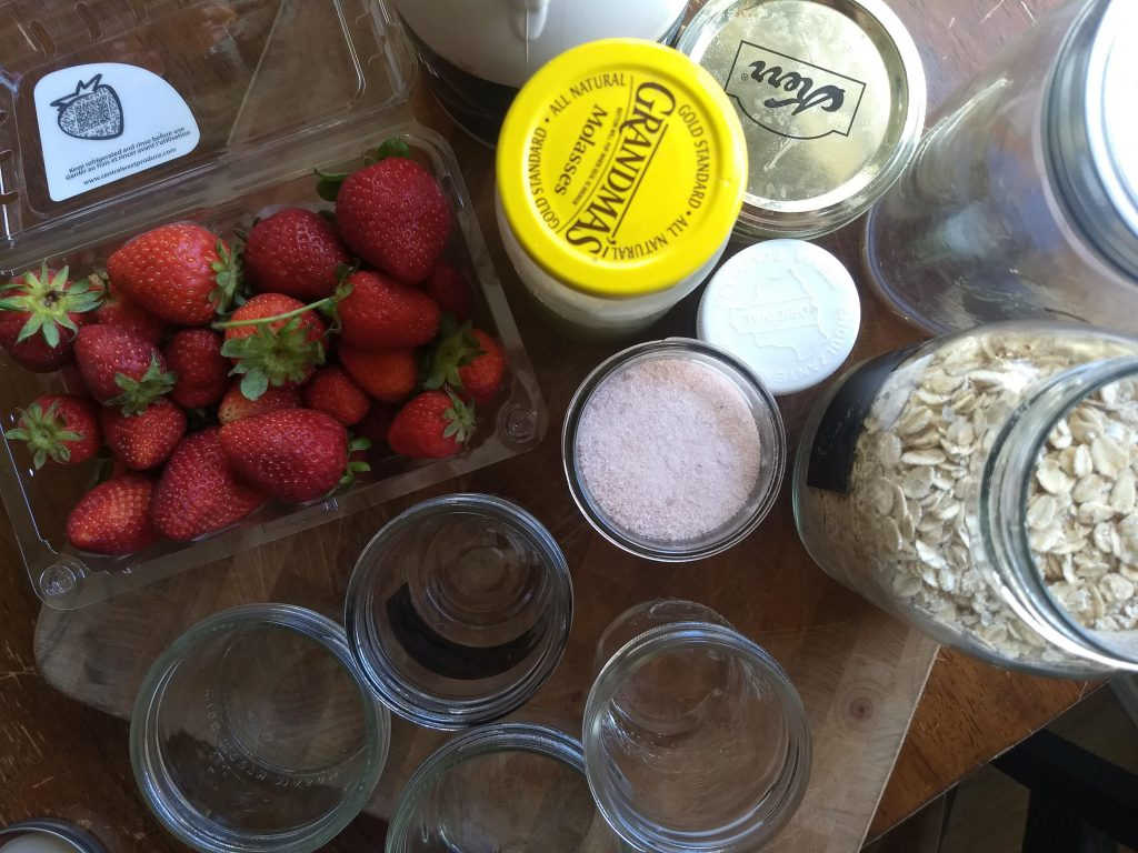 The ingredients for strawberry overnight oats on a cutting board