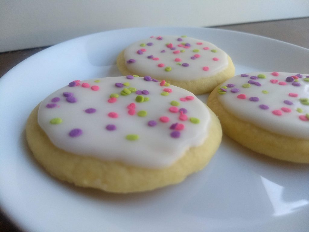 white frosted round sugar cookies on plate