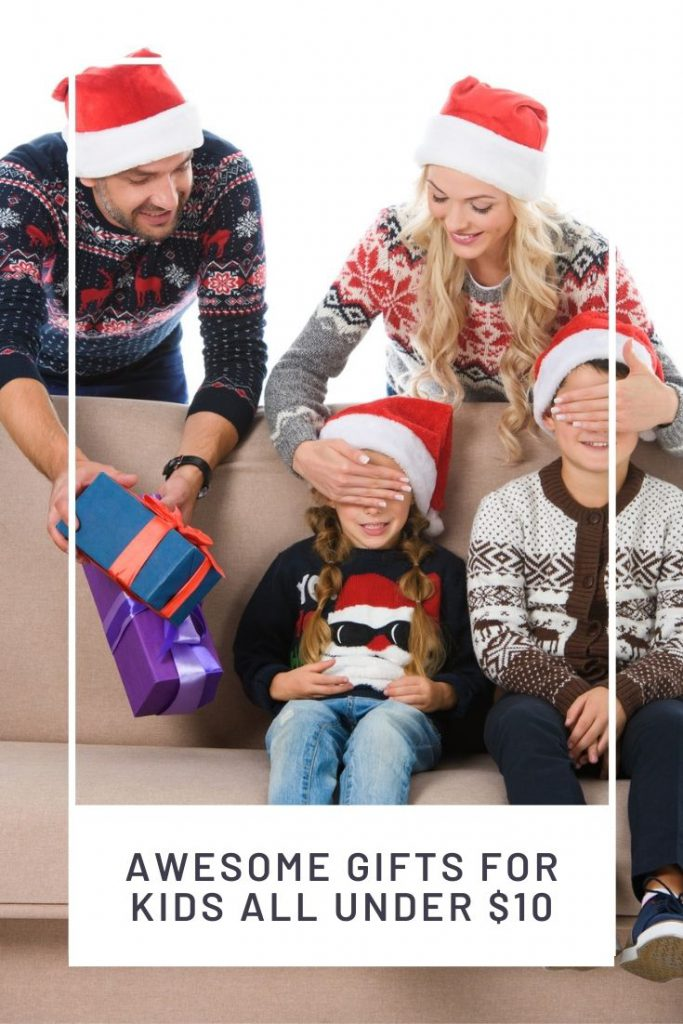 two kids sitting on a couch and parents giving them gifts
