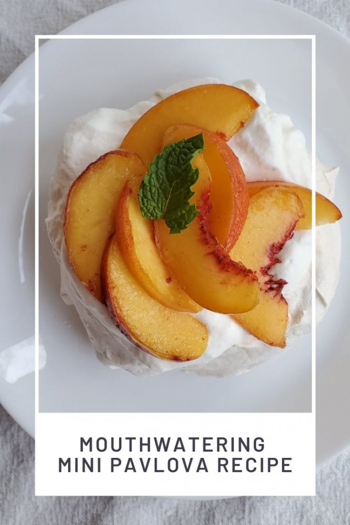 Mini Pavlovas topped with peaches and a sprig of mint