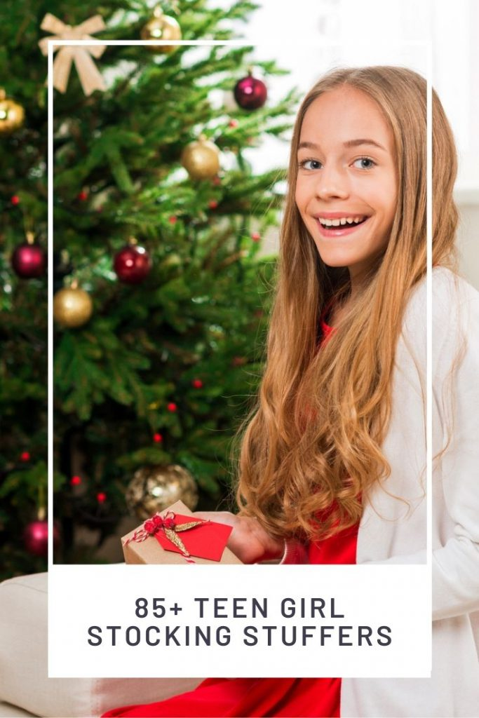 Teen girl sitting in front of a Christmas tree