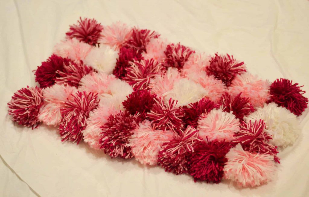 Red and pink pom pom rug