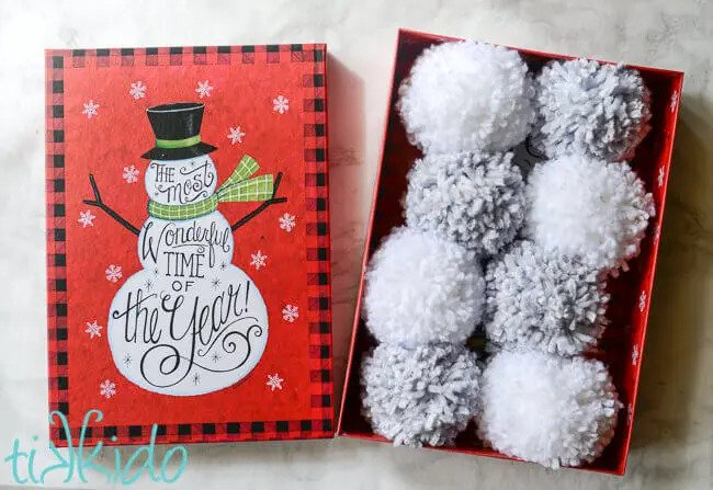 a red box with white pom pom snowballs