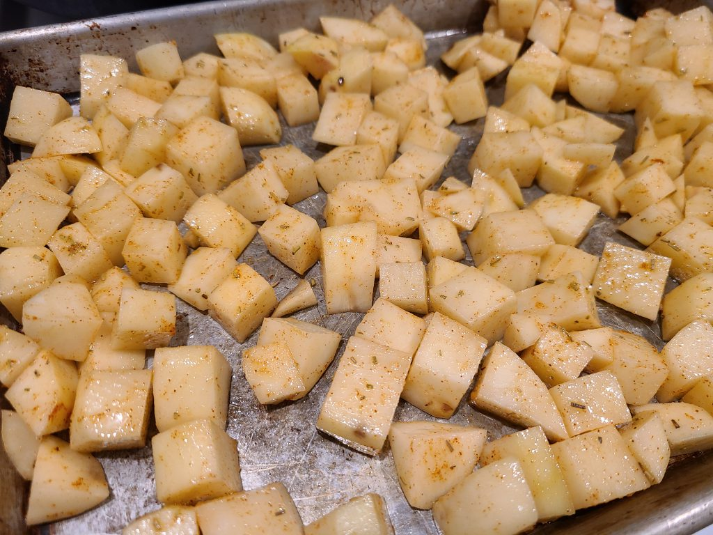 Baked home fries on a pan ready to go into the oven