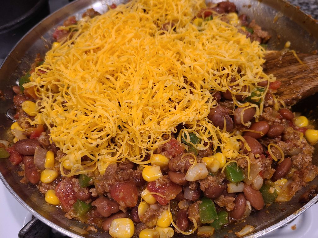 Taco pot pie ingredients in a skillet topped with cheese